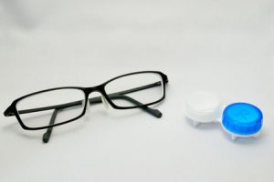 a pair of eyelgasses and contact lens case side by side